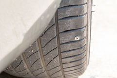 nail puncturing tire. Royalty Free Stock Images