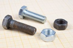 Screw and Nuts on graph paper. Background Stock Images