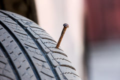 Screw puncturing tire close up Royalty Free Stock Photography
