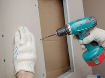 is screwed through the electric screwdriver Stock Images
