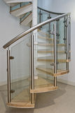Screw stair. Solid newel stairs with wooden steps, ang glass and steel rail Royalty Free Stock Photos