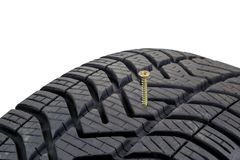 A screw stuck in a car tyre Royalty Free Stock Photos