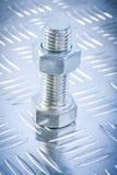 Screwbolt и продетая нитку гайка конструкции на рифлёной задней части металла Стоковое Изображение RF
