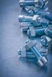 Screwbolts et écrous filetés sur le fond métallique rayé Co Photo libre de droits