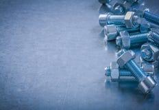 Screwbolts och muttrar på skrapad metallisk bakgrundsconstructio Royaltyfri Foto