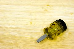 Screwdriver. Small flathead screwdriver on wood grain background Royalty Free Stock Image