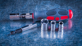 Screwdriver bit holders replaceable heads on. Scratched metallic surface close up view construction concept Stock Image