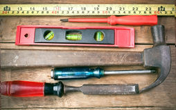Screwdriver, hammer, tape measure placed on the wooden floor. Royalty Free Stock Photo