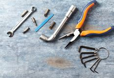 Screwdriver, hex keys, socket wrench and bits for a screwdriver on rustic wooden background. stock images