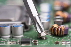 Screwdriver and mainboard Stock Photo