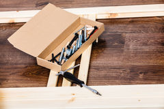 Screwdriver and nails for furniture assembling. Royalty Free Stock Photo