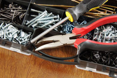 Screwdriver and pliers lie on a plastic box with many screws Stock Photo