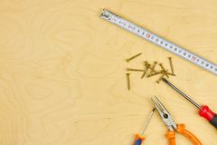 Screwdriver and pliers with screws lie on the plywood. copy space. DIY concept royalty free stock image