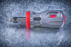 Screwdriver with replaceable bits on metallic background constru Stock Image