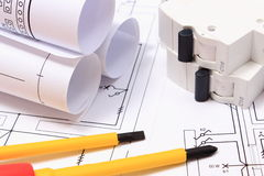 Screwdriver, rolls of diagrams and electric fuse on construction drawing Royalty Free Stock Image