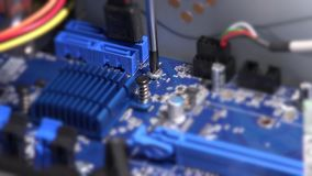 Screwdriver bolt on computer motherboard. Computer warranty works. Static closeup shot. 4K UHD stock video footage