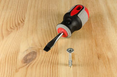 Screwdriver and a screw halfway into wood Royalty Free Stock Photography