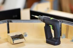 Screwdriver with screws and furniture at workshop Stock Photo
