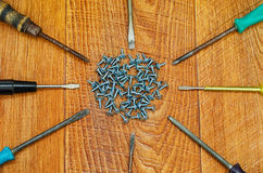 Screwdriver and screws. Many screwdrivers and screws closeup on background of wooden planks Stock Photography