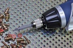 Screwdriver with screws on a metal surface Stock Photos