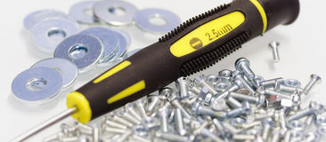 Screwdriver with screws, nuts and washers Stock Images