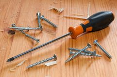 Screwdriver and screws. A screwdriver and some screws on a wooden table Royalty Free Stock Image
