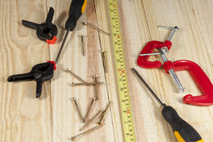 Screwdriver, screws and a tape measure laying on a wooden floor Royalty Free Stock Photo