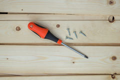 Screwdriver and screws on top of wood boards Royalty Free Stock Photography