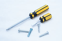 Screwdriver and screws. Two screwdriver and some screws on white blackground Stock Images