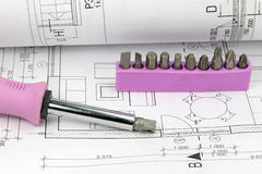 Screwdriver and set of bits on the blueprint Stock Photography