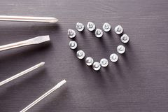 Screwdriver set with screws laid out in the shape of a heart on gray wooden table. the concept of father`s day, men, DIY Royalty Free Stock Image
