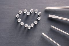 Screwdriver set with screws laid out in the shape of a heart on gray wooden table. the concept of father`s day, men, DIY Stock Images