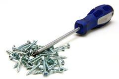 Screwdriver and small metal screws Royalty Free Stock Photos