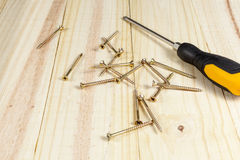 Screwdriver and some crosshead screws laying on a wooden floor Stock Images