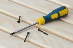 Screwdriver and three screws over wood Royalty Free Stock Images