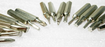 Screwdriver tips. Scatterd on the white table. Able to use as background Royalty Free Stock Photo