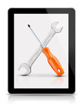 Screwdriver and wrench on tablet Stock Images