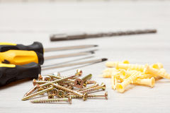 Screwdrivers, drill and screws on white wooden background stock photos