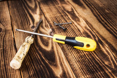 Screwdrivers and screw on woodwn background Stock Photo
