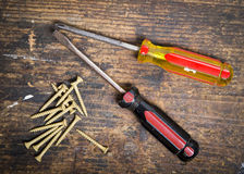 Screwdrivers and screws. A phillip driver and screws on a wood workbench Stock Photo