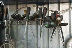 Screwdrivers on a stand in a dirty workshop Stock Photography