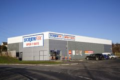 Screwfix与停车场和蓝天背景的商店前面 库存照片