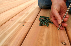 Screwing Decking. A hanywoman screws on new cedar decking. Copy space on left royalty free stock image