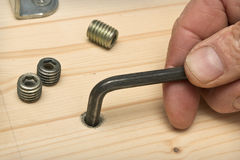 Screwing furniture fasteners in a wooden shield Royalty Free Stock Photography