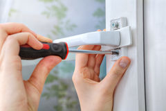 Screwing the screw of window handle on pvc window. Royalty Free Stock Photography