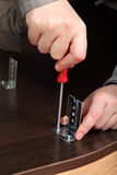 Screwing screws with a hand screwdriver, mount furniture fitting Stock Image