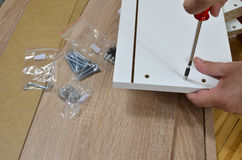 Screwing Wood Screw. Screwing a wood screw in a drawer element using a screwdriver Stock Images