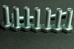Screws. Row of steel screws on black background Stock Photography
