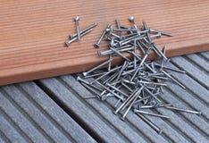 Screws. Pile of screws on a floorboard Royalty Free Stock Image
