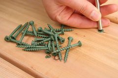 Screws. Screwing on new cedar decking royalty free stock photo